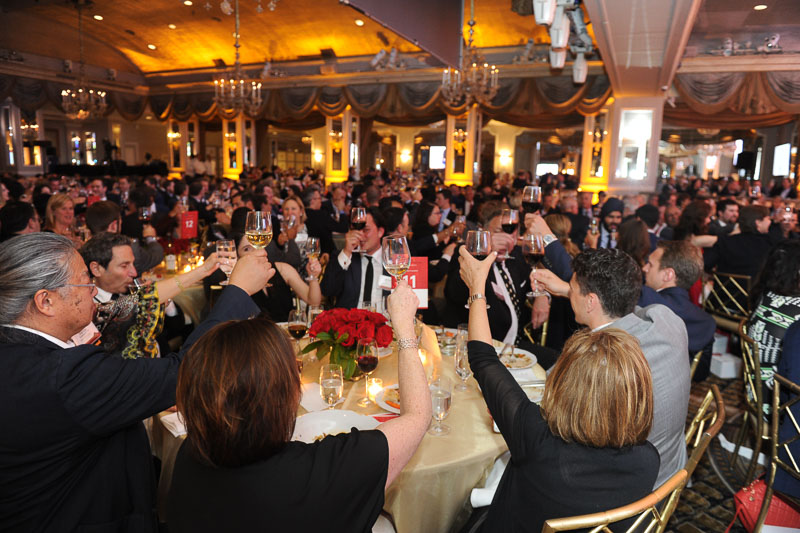 Photo of the people in the banquet hall raising their glasses for a toast