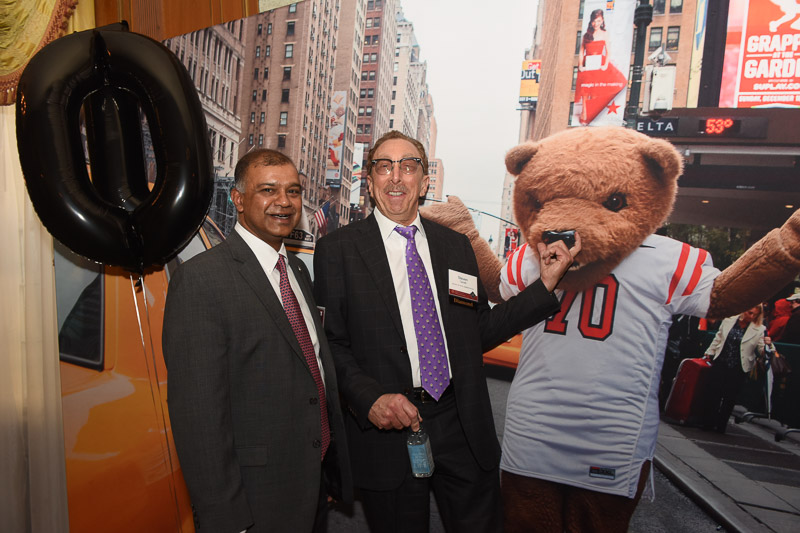 Photo of two men and touchdown the bear on a NYC street