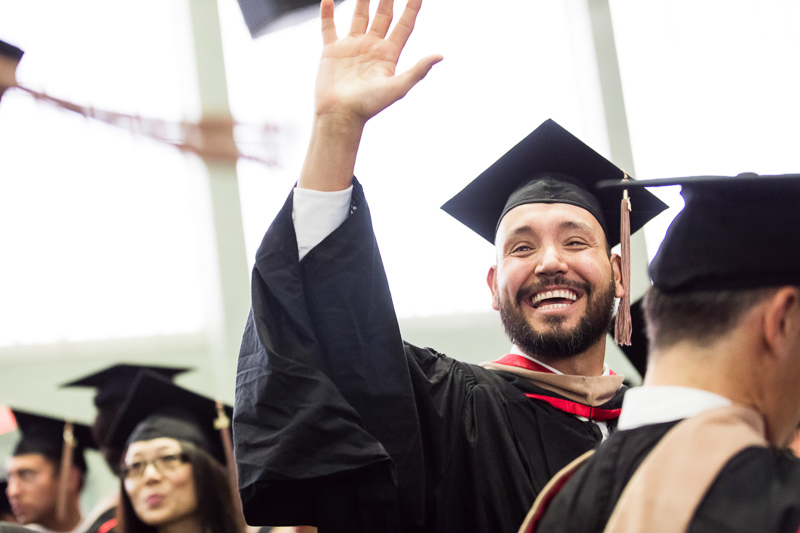 Photo of a graduate waving