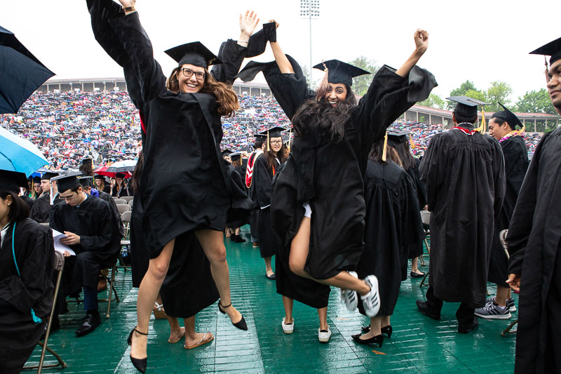 Photo of two graduates jumping in the air