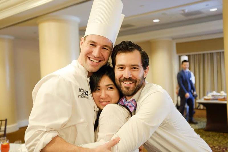 Photo of three students in chef's attire hugging
