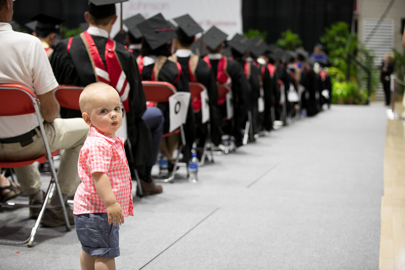 Photo of a baby standing in the aisle amongst graduates