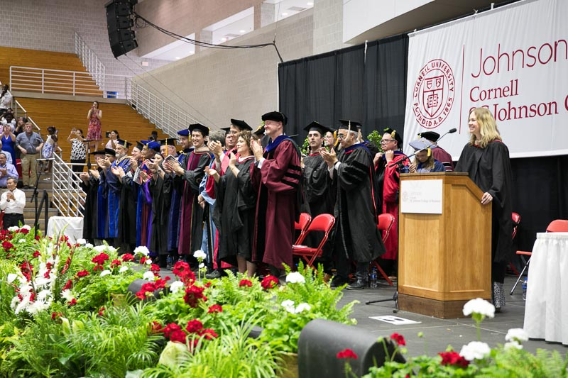 Photo of Johnson faculty applauding graduates