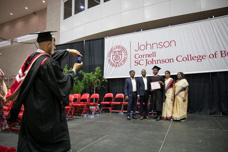 Photo of a graduate and his family under the Johnson banner