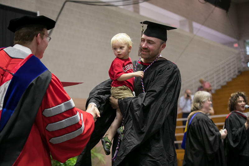 Photo of a graduate holding a child