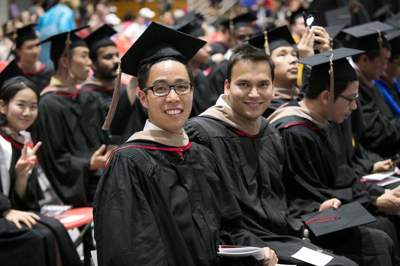 Photo of seated, smiling graduates