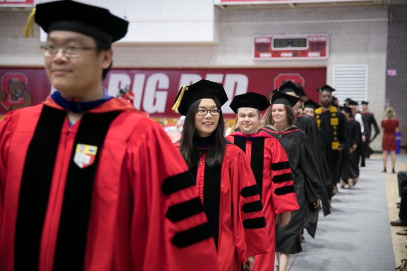 Photo of walking PhD gradautes