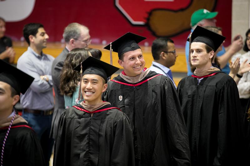 Photo of walking, smiling graduates