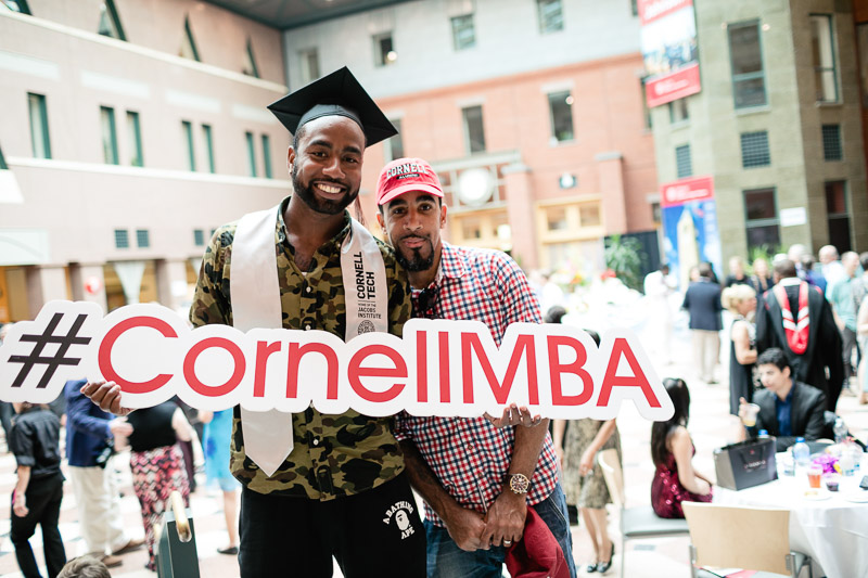 Photo of a graduate holding a #cornellmba sign