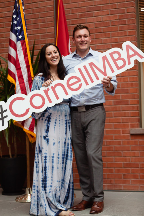 Photo of a man and women holding a #cornellmba sign