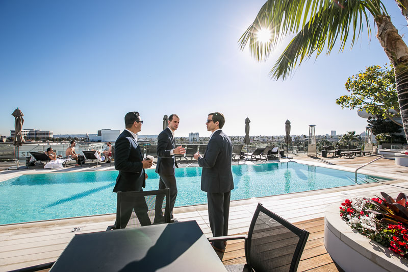 Photo of three men wearing suits and talking near a pool