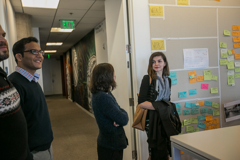 Photo of two women looking at a wall of post-it notes
