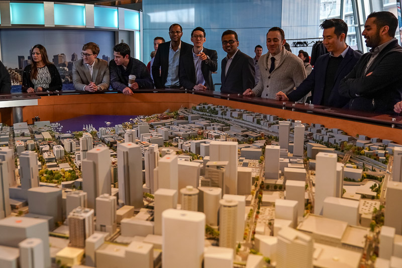Photo of a close up of a scale model of a large city; students looking in the background