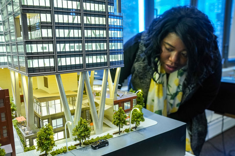 Photo of a woman looking at a model of a building
