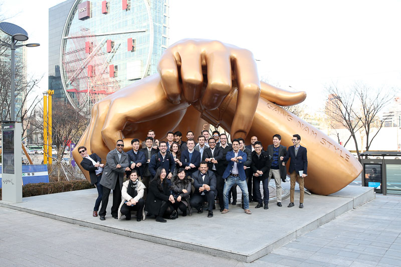 Photo of the group under an enormous statue of a hand on a plaza