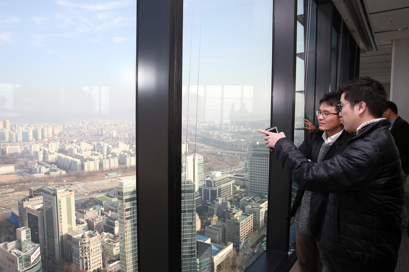 Photo of a man looking out a window and pointing from a high rise