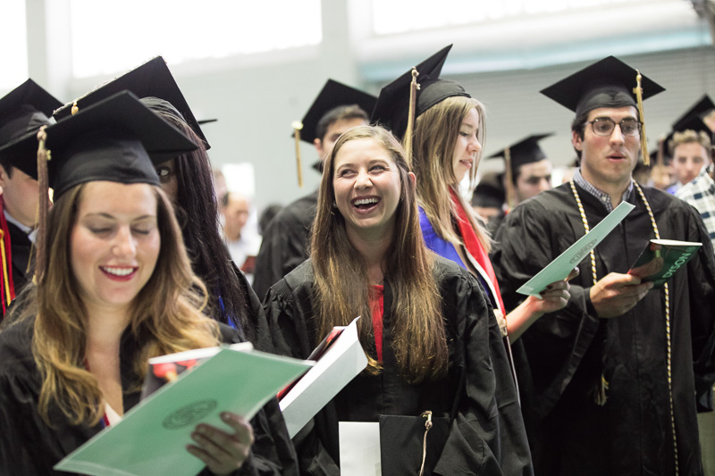 Photo of a smiling graduate standing in line