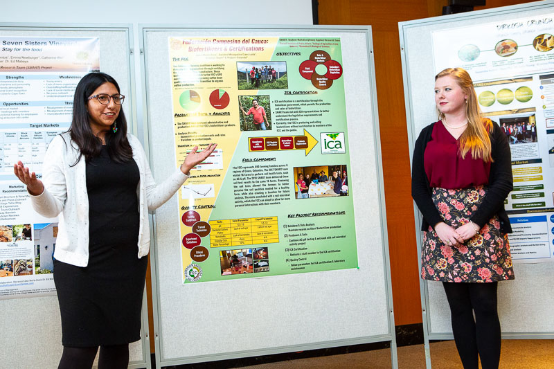 Photo of two females presenting with posters