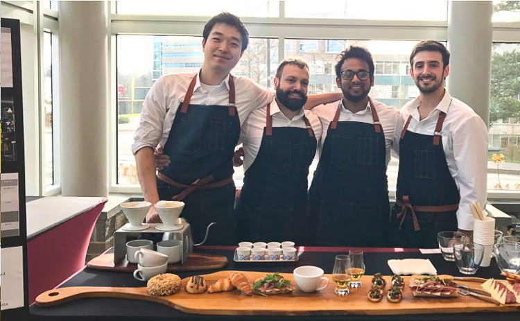 Photo of four students standing behind a table of food wearing aprons