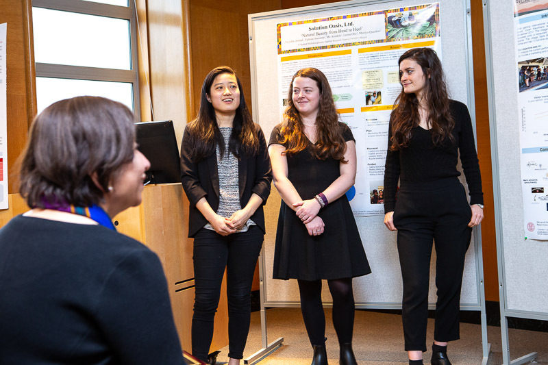 Photo of three female students presenting at the front of the room with posters