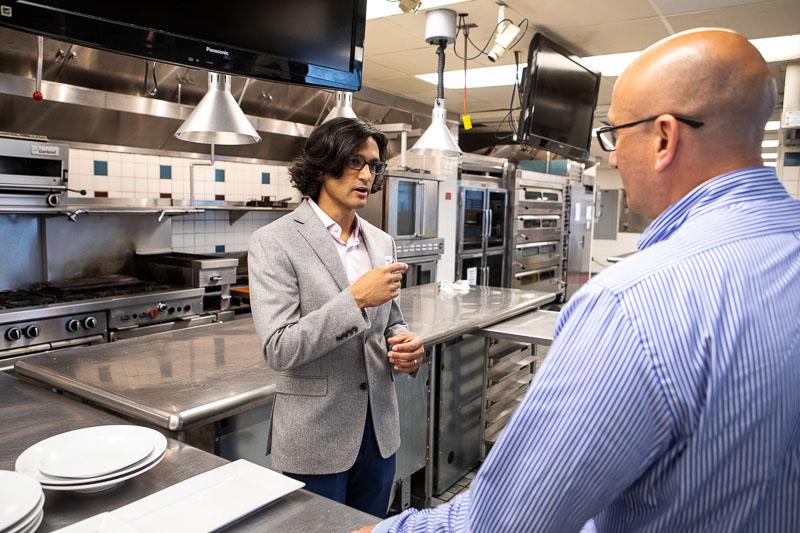 Photo of Aaron speaking in an industrial kitchen