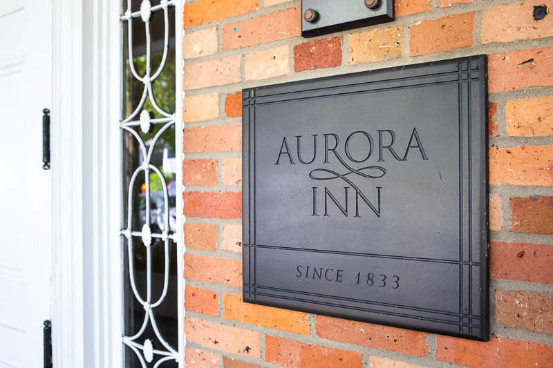 Photo of the sign by the front door that says Aurora Inn