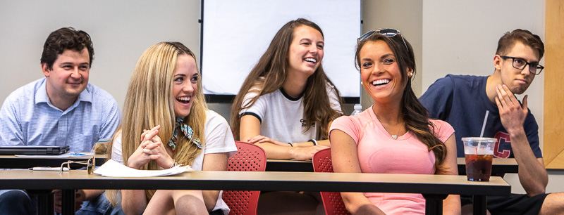 Photo of five students sitting behind a desk and laughing