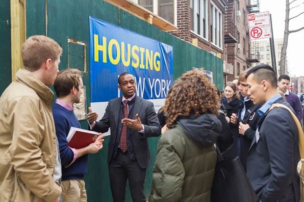 Photo of students standing with a speaker outside next to a Housing NYC sign