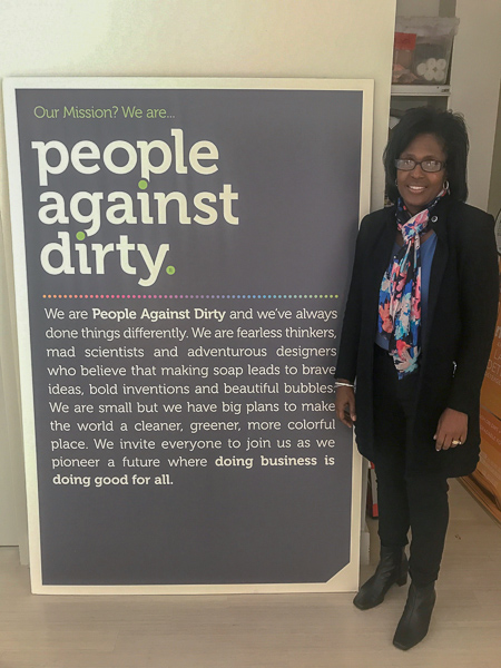 """Photo of Lynn Wooten standing next to a sign at Method that says """"People against dirty"""""""