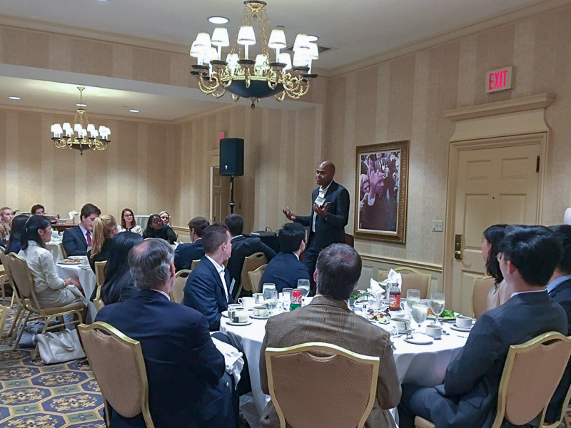 Photo of a man speaking at the front of a banquet room