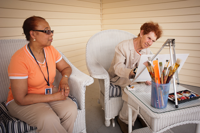 Photo of a resident painting with her caregiver