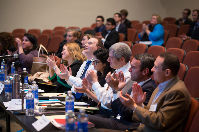 Photo of faculty clapping in an auditorium after a presentation