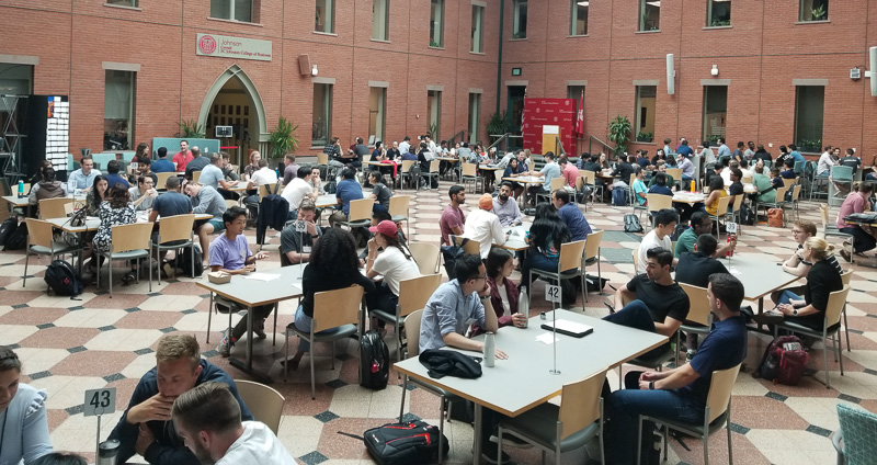 Photo of a packed Dyson Atrium with students working at tables