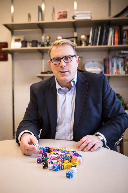 Photo of Vince Slaugh seating with a pile of dice on the table