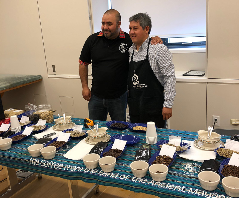 Argueta and Lopez behind their table at the coffee tasting event