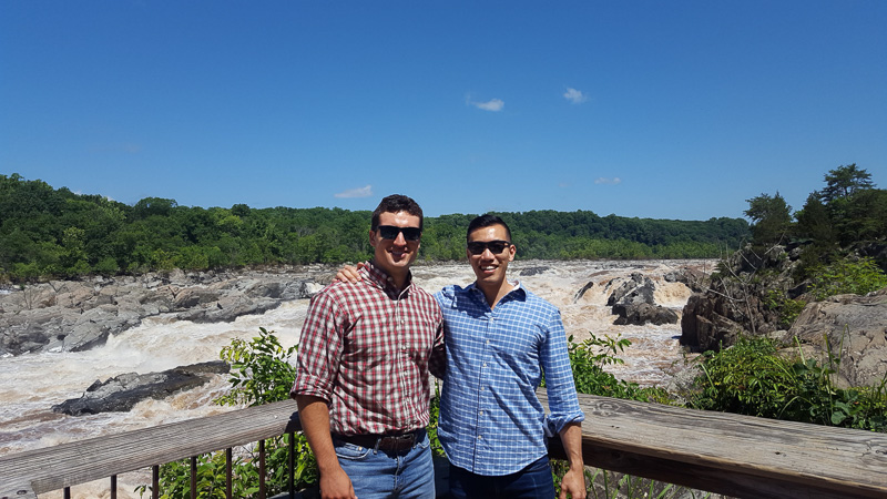 Keith and his co-consultant standing on a deck overlooking a section of rapids