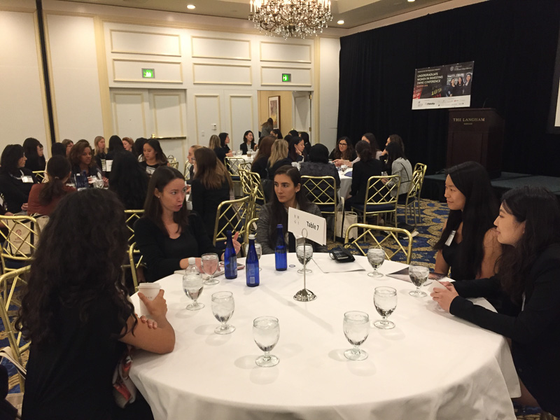 Students sitting around tables networking