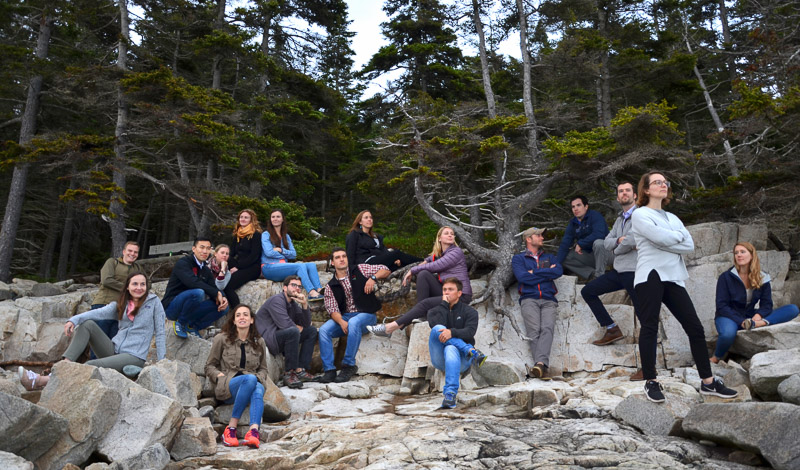 Interns in a group photo on boulders