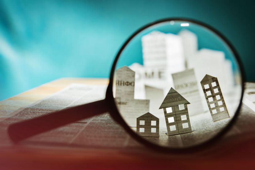 magnifying glass showing real estate buildings over a contract