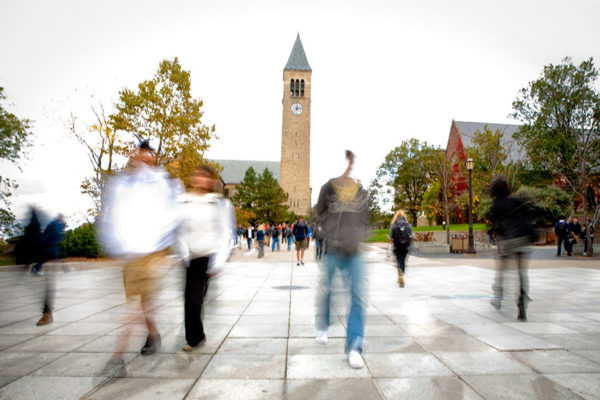 Blurred students walking in front of Cornell's Clocktower