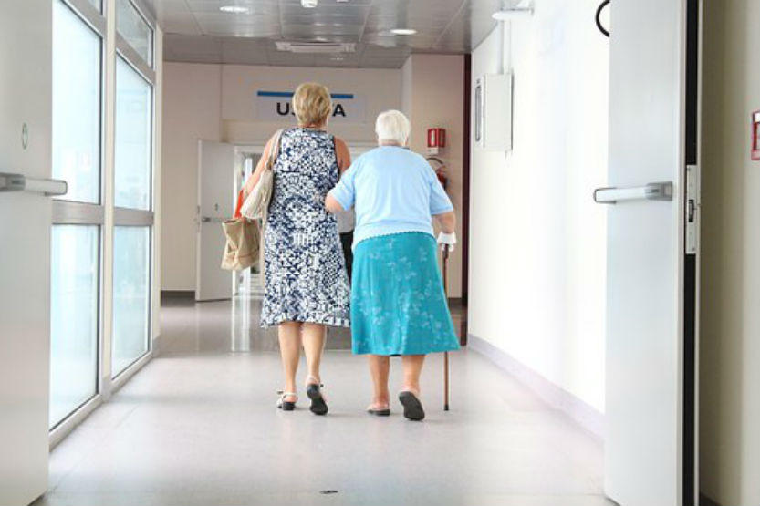woman helping elderly senior down hallway