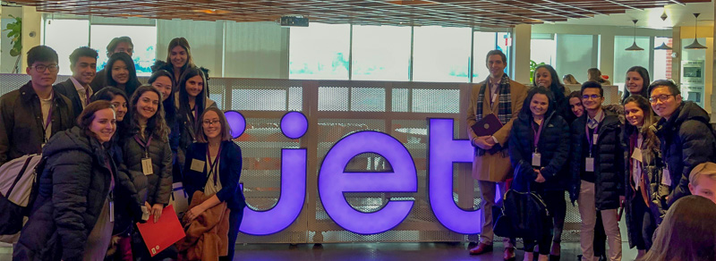 Large group standing around a jet sign