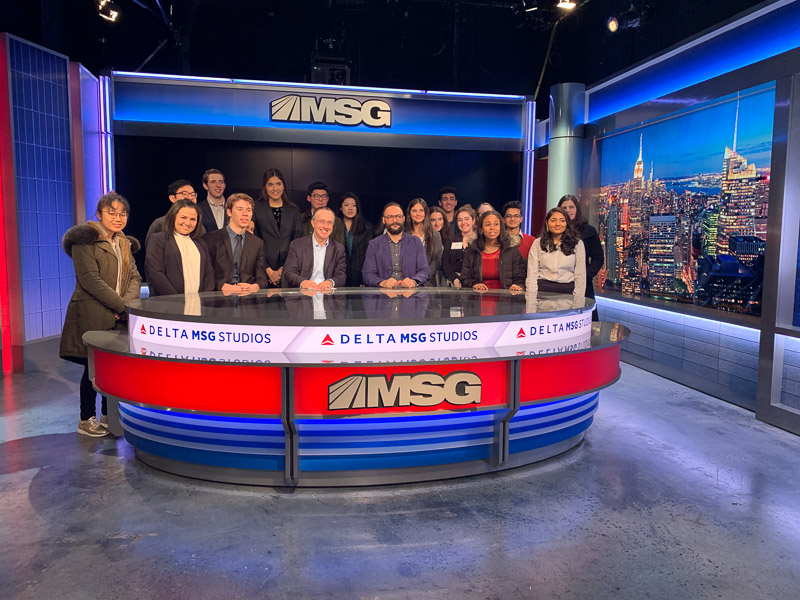Students standing around the MSG desk in the studio