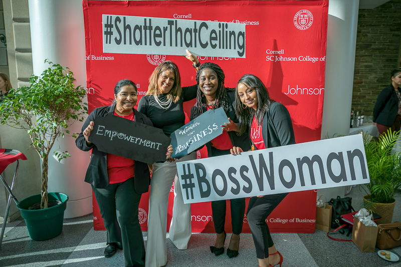 Four women pose with #bosswoman signs