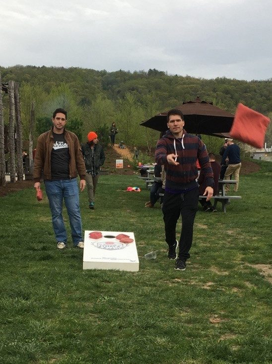 Two men play corn hole