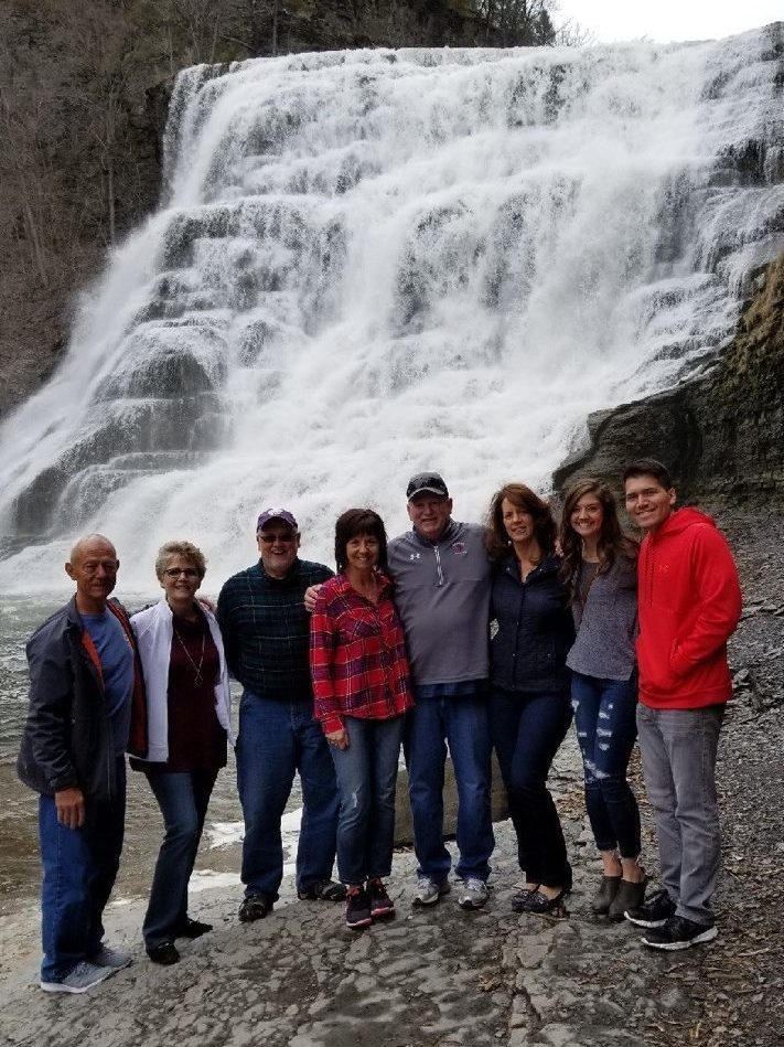 A groups stands in front of a waterfall