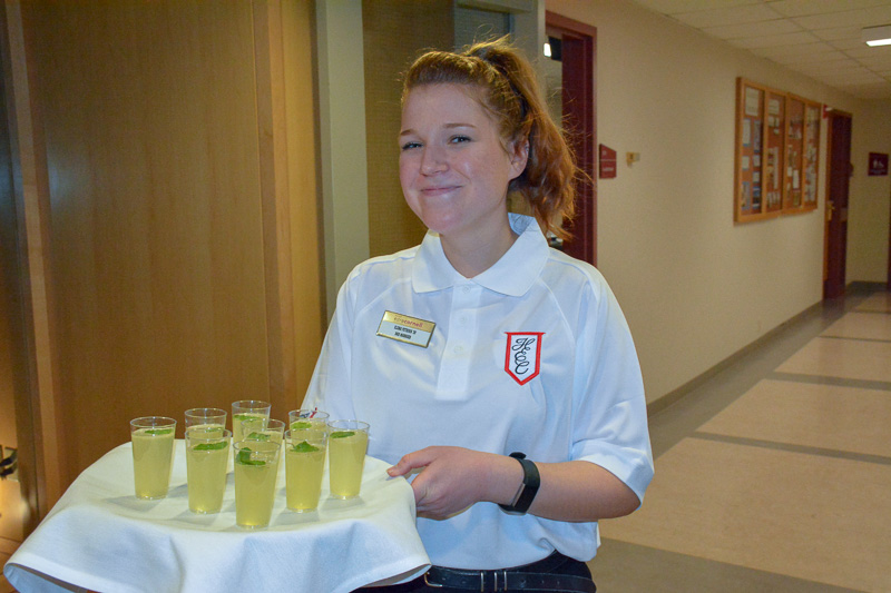A student holding a tray of drinks