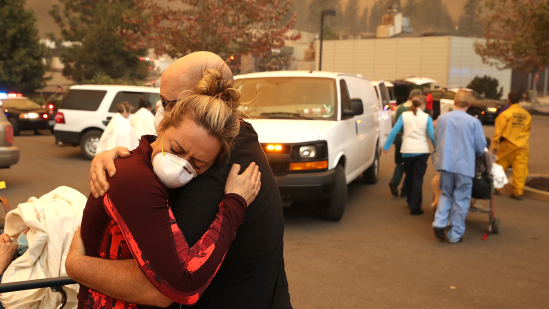 Coworkers hugging among smoke and rescue vehicles
