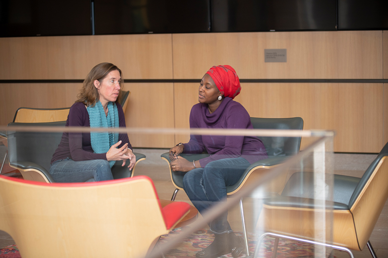 Joanna and Khadijat talk while seating in a lobby