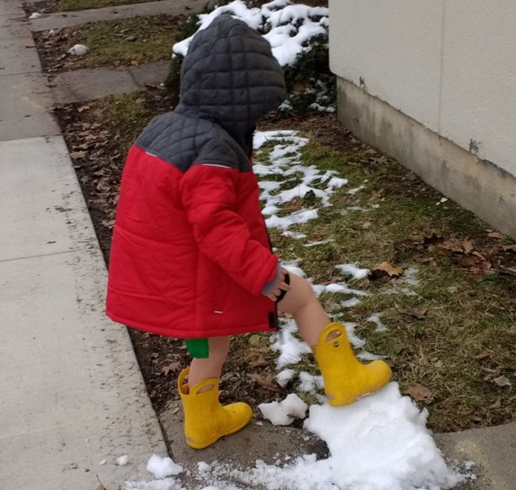 Gabe Sudduth's son plays in the snow, despite wearing an outfit that does not match Ithaca's winter temperatures.